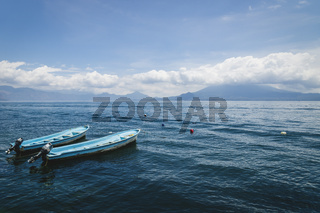 Two blue boats on lake Atitlan with view on volcanic mountainrange in Santa Cruz la Laguna, Guatemala