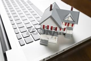 Miniature House on Laptop Computer