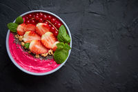 Summer berry smoothie or yogurt bowl with strawberries, red currants and chia seeds on black