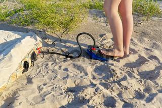 A woman with air foot pump pumps an inflatable mattress or air bed at sandy beach. Foot inflates air mattress with foot pump on sand.