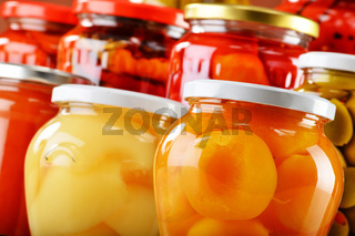 Jars with fruity compotes jams and pickled vegetables. Preserved fruits