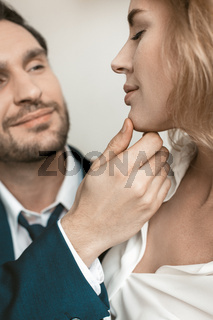 Passionate couple in the office at the workplace. Man holds a girl by the chin. They smile . High quality photo