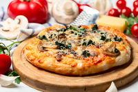 Pizza with tomatoes, mushrooms, cheese and green basil.