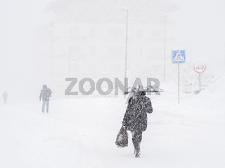 A woman with an umbrella walks along a snow-covered road following other people during a heavy snowfall