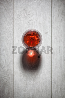 Glass of red wine on wooden table.