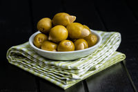 Pitted green olives stuffed with almonds in bowl.