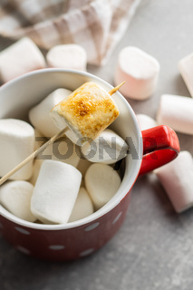 Grilled sweet marshmallows in mug.