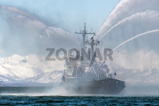 Salvage ship spraying water on sea for supporting emergency case of fire