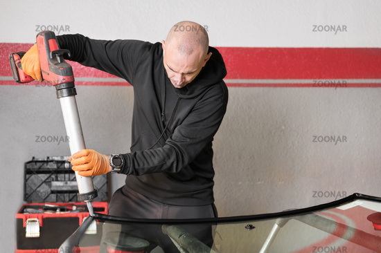 Glazier applying rubber sealing to windshield in garage, close up.