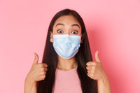 Covid-19 pandemic, coronavirus and social distancing concept. Close-up of excited and amazed pretty asian girl support great idea, praise nice choice or compliment, show thumbs-up, wear medical mask