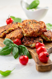 Zucchini pancakes or fritters with caramelized tomatoes.