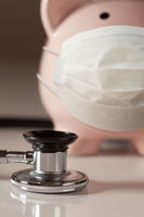 Stethoscope and Piggy Bank Wearing Protective Medical Face Mask