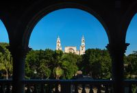 View through arches to the cathedral of Merida over the main square park 'Plaza Grande' in Merida