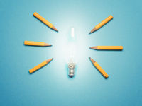 A glowing light bulb with 6 pencils as light rays, New ideas or creativity concept on blue background