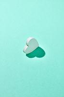 One gypsum Valentine's heart with hard shadow.