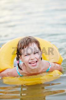 Mädchen mit Schwimmreifen im Wasser