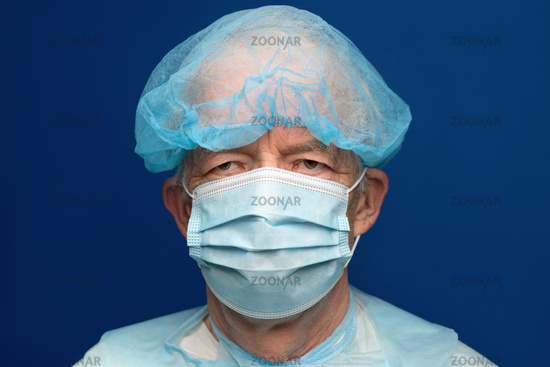 Portrait of senior adult dressed in surgical face mask, covering nose and mouth from SARS