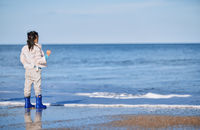 Cute girl wearing rubber boots next to the ocean