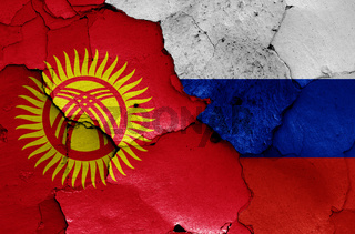 flags of Kyrgyzstan and Russia painted on cracked wall