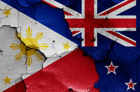 flags of Philippines and New Zealand painted on cracked wall
