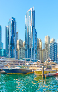 Harbour with boats amd modern towers of Dubai Marina