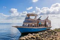 Old ship near stony shore floating in sea water near rocky coast against cloudy sky