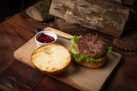 Fresh craft beef burger with cherry sauce in a sauce bowl, fresh lettuce with lead bun laying next with wooden lodges as decoration. Restaurant concept. Street food concept