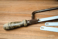 an old hand hacksaw with several spare saw blades