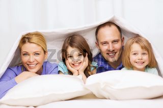 happy family with two kids under blanket at home