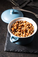 Mix of legume beans and chickpeas with sauce in pot.