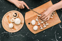 Champignon mushrooms on a wooden board. Cutting mushrooms to prepare delicious food for dinner. Fresh chopped mushrooms.