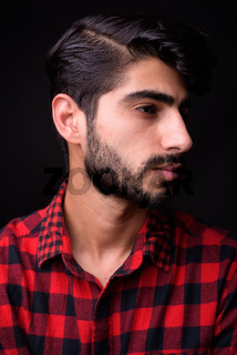 Young handsome bearded Persian man against black background