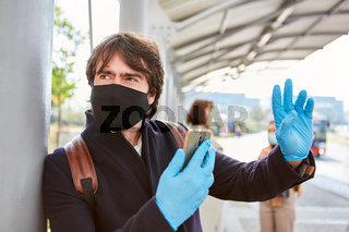 Pendler mit Mundschutz wegen Covid-19 und Smartphone