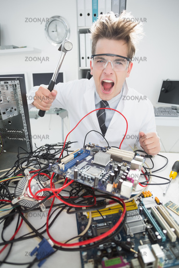 Angry computer engineer holding hammer over console