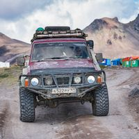 Old four-wheel drive vehicles Nissan Patrol driving mountain road on background volcanic landscape