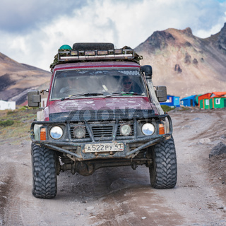 Old four-wheel drive vehicles Nissan Patrol driving on rocky mountain road on background volcanic landscape. Expedition in travel destinations to volcano