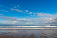 A sandy beach with big waves and a small rainbow in an expressive sky