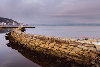 Quay wall with lighthouse of the Trondheim port on overcast winter day