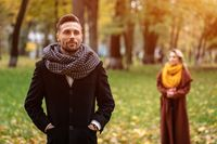 Man stands in a coat and a scarf in the park waiting for his girlfriend or wife who stands behind him or looks like him from the back. Young couple outdoors in a park on a beautiful autumn day