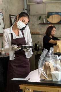 Waitress with face mask take order for curbside pick up and takeout.