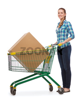 smiling young woman with shopping cart and big box