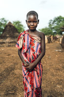 TOPOSA TRIBE, SOUTH SUDAN - MARCH 12, 2020: Girl wrapped in floral fabric looking and camera and smiling while living in Toposa Tribe village in South Sudan, Africa