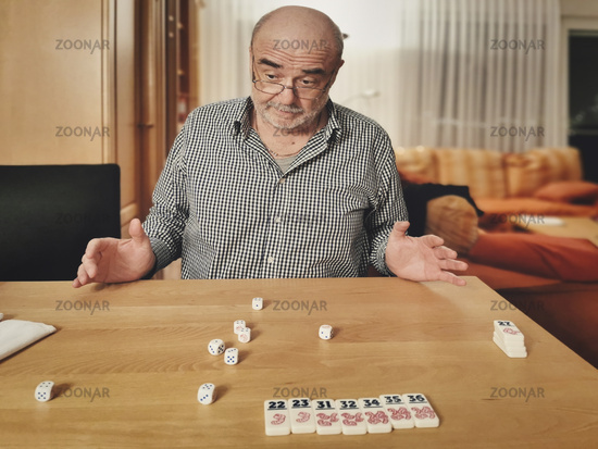 Senior sits at the table and rolls the dice
