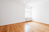 empty white room in apartment flat with hardwood floor and window