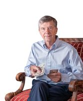Senior man facing camera and counting out US dollar bills as though handing to viewer