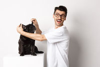 Happy young man looking at camera, showing cute dog ears and feeling rejoice, adopting a pet, standing over white background