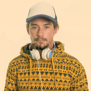 Studio shot of young handsome man wearing cap and headphones around neck isolated against white background