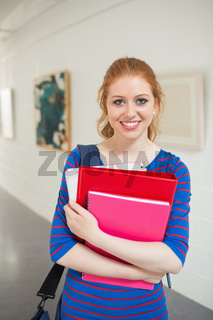 Smiling student holding folders in the hall looking at camera