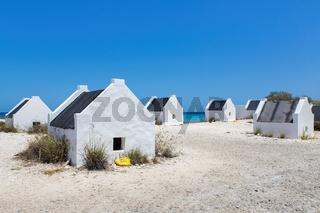 Group of white slave houses on bonairean beach