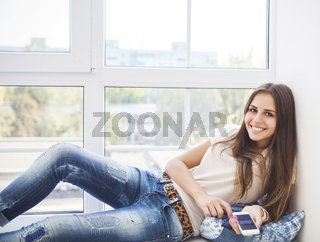 Teen student girl with smartphone at home
